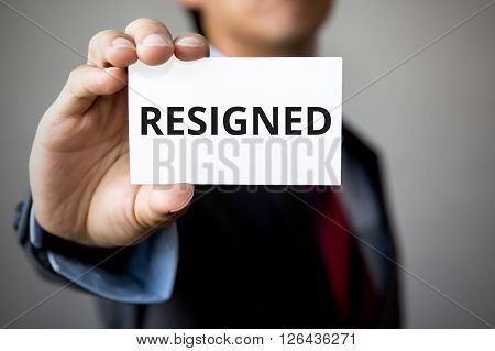 Businessman Presenting 'resigned' Word On White Card