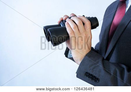 Close-up Of Businessman Looking For Something With Binoculars Such As Business Opportunities / Jobs