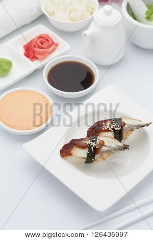 Eel Sushi Nigiri With Ginger Wasabi And Soy Sauce On A White Plate