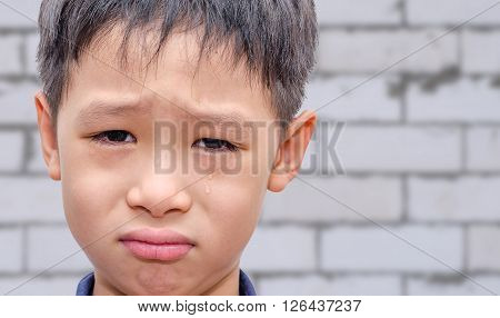 Young Asian boy crying over brick wall background