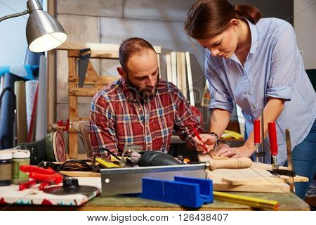 Young couple tinkering in home workshop, busy.