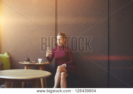Attractive female watching video or reading business weblog in network on cell telephone caucasian businesswoman cheking e-mail on her smart phone while is relaxing during work break in coffee shop