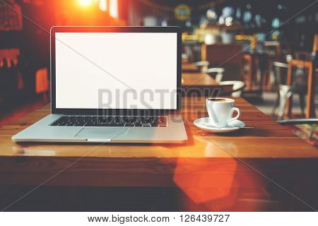 Open net-book and cup of cappuccino lying on table in cafe bar interior laptop computer with blank copy space for your text message or promotional content freelance remote job during coffee break