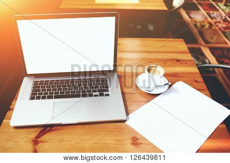 Open laptop computer and sheet of paper with copy space for your text message on advertising content net-book and cup of coffee lying on wooden table in contemporary interior education via internet