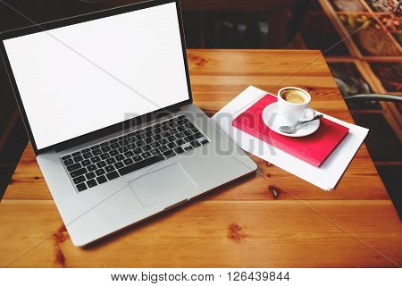 Open laptop computer with blank copy space screen for your information content or text message portable net-book with cup of cappuccino lying on wooden table in contemporary coffee shop interior