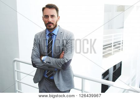 Young serious man lawyer in formal wear is standing with crossed arms in modern office interior. Handsome bearded male skilled manager dressed in classic suit is waiting beginning of the conference