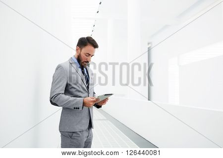 Male proud CEO is reading world news in network via touch pad while is standing in hallway company near copy space for your advertising text message. Successful businessman is using digital tablet