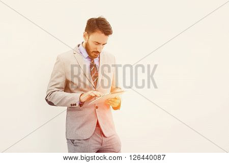 Young successful businessman or experienced leadership is searching information on web site via touch pad for meeting with employeeswhile is standing near copy space for your advertise text message