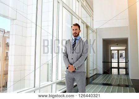 Young man proud managing director dressed in luxury suit is standing in corridor of his successful enterprise.Male serious business worker in formal wear is posing for camera in modern office interior