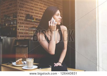 Portrait of a lovely young woman talking on cellphone while relaxing in coffee shop during breakfast. Pretty latin female having mobile conversation while resting in sidewalk cafe after mall shopping