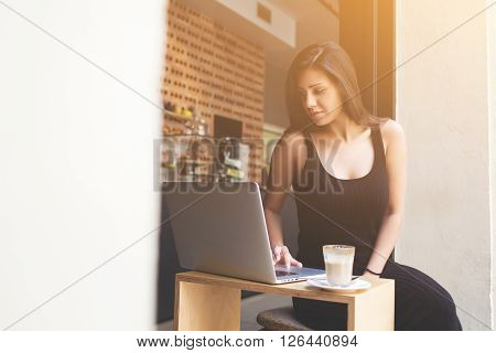Young female freelancer engage in remote work in internet by using her laptop computer during breakfast in cafe. Gorgeous latin woman connecting to wireless via net-book while breakfast in coffee shop