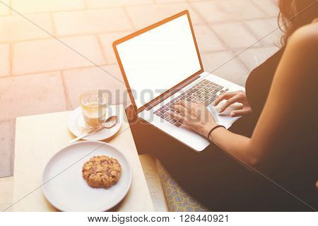 Cropped image of young female student searching information in internet by net-book while sitting in sidewalk coffee shop. Young woman is using laptop computer with blank copy space screen for content
