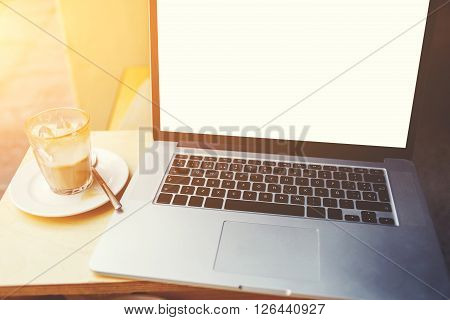 Cropped image of open net-book with screen for information content or advertising text message laptop computer lying near cup of coffee on wooden table in sidewalk cafe