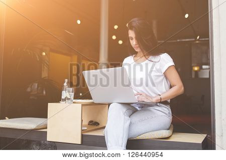 Young female freelancer is working on net-book while breakfast in modern coffee shop with contemporary design. Charming latin woman is connecting to wireless for browsing internet on laptop computer