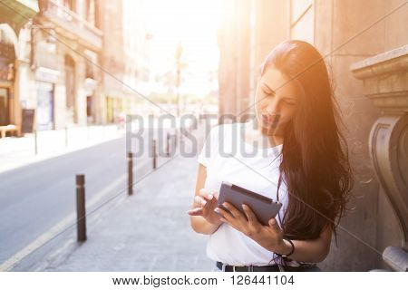 Gorgeous female tourist is using digital tablet for navigation during summer trip abroad charming woman wanderer is searching information in network on touch pad while is standing on the city street