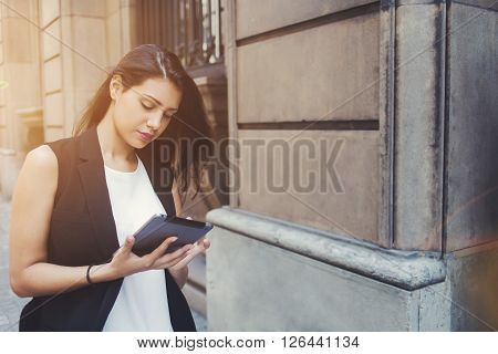 Young female tourist is viewing photos thats she just took on touch pad camera during walking tour in the city beautiful woman is searching information in network while is using her digital tablet