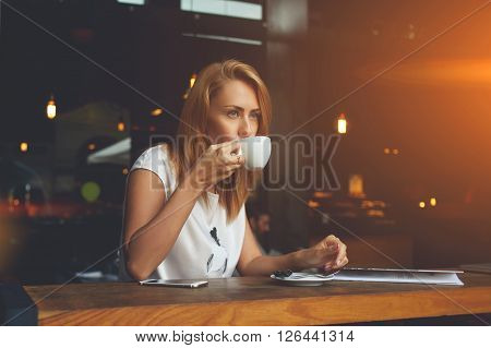 Young pretty European woman drinking cappuccino while relaxing in modern cafe bar after work day dreamy female enjoying cup of tea while sitting in cozy coffee shop during her recreation time
