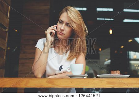 Upset female having cell telephone conversation while is sitting in restaurant and waiting for her order annoyed young woman calling with smart phone to her husband which does not respond to the call