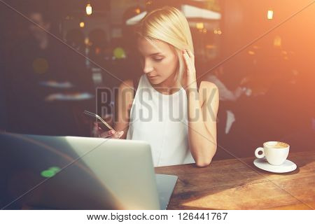 Young beautiful hipster girl reading text message on mobile phone while sitting with net-book in cafe charming female student using cell telephone and laptop computer during rest in coffee shop