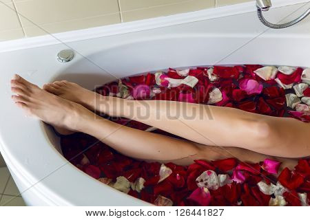 legs of a young girl lying in a white tub with red rose petals