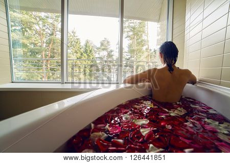 young brunette girl with long hair is a white Jacuzzi bath with rose petals and looking out the big window behind which are trees