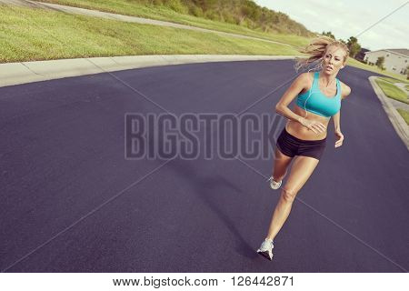 Instagram style photo of a beautiful fit and healthy blond woman road running while listening to music on her portable mp3 player