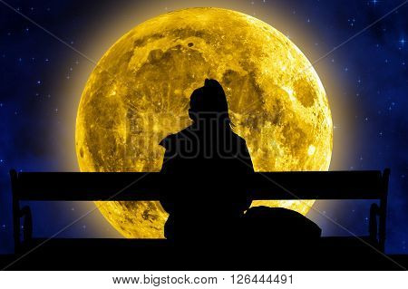 Girl sitting on a bench and watching the Moon and stars.
