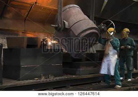 workers with helmet inside a foundry at work