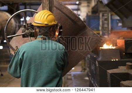 workers with helmet working  inside a factory