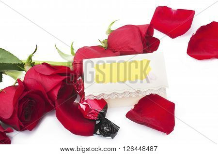 Red roses and candy with a blank gift card on a white background