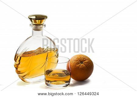 Bottle and a glass of whiskey with an orange on a white background