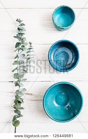 Three different  turquoise empty ceramic empty plates and evergreen branch on a white wooden background. Top view on set of trendy empty plates. Organic food, healthy life, pottery, decoration concept