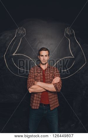Serious Young Man With Drawn Muscular Arms On The Background Of Chalkboard