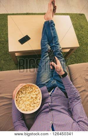 Top View Of Barefoot Man Lying On Couch And Watching Tv With Popcorn