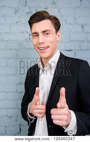 Portrait Of Handsome Young Man In Suit Pointing On Camera