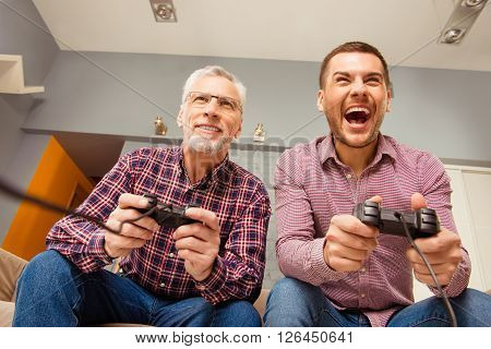 Close up portrait of two excited handsome men playing video game at home