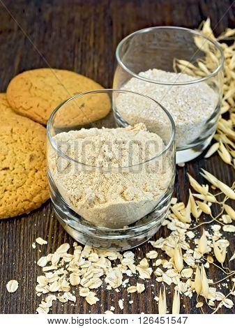 Flour and bran small oat in a two glassful, oatmeal and ears, cookies on a background of wooden boards