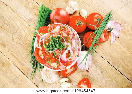 healthy food : fresh tomato salad in white bowl with bunch of chives and raw tomatoes on twig , onion, and garlic over wooden table