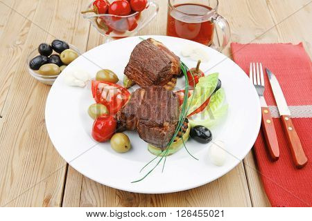 grilled meat : beef ( lamb ) garnished with tomatoes , green and black olives, tomatoes and juice on wooden table