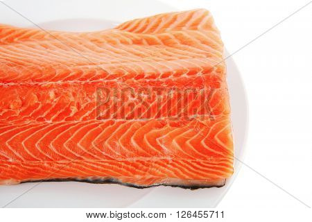fresh uncooked salmon fillet on white plate