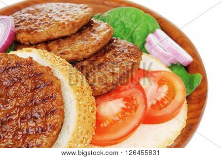several large hamburger with loaf on wooden plate isolated over white background