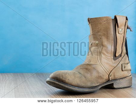 Patina Engineer Leather Boot on wooden surface and blue background with space for text