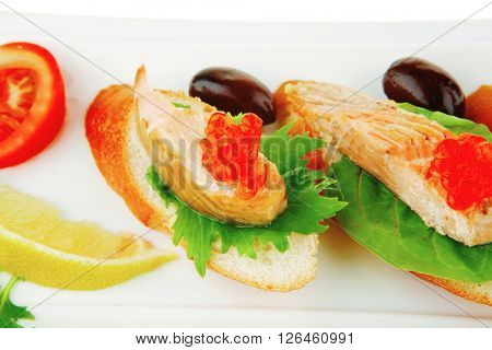 small salmon sandwiches served with caviar and olives