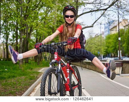 Bikes cycling girl wearing helmet with legs apart.