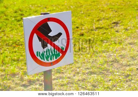 The prohibitive sign on the label Do not walk the lawn - closeup against tha lawn in sunlight