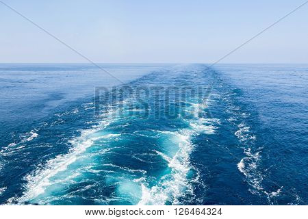 Blue wake of cargo vessel on the sea water surface.