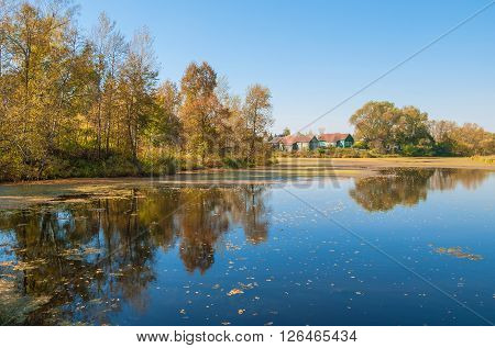 Autumn landscape with a small village on the river bank