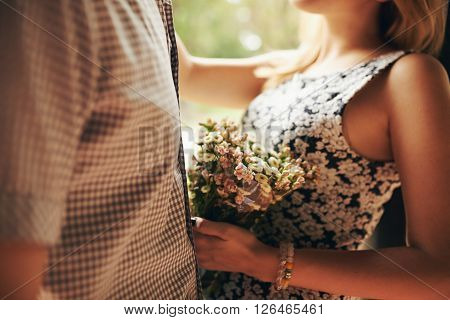Cropped image of woman with bouquet of flowers hugging her boyfriend