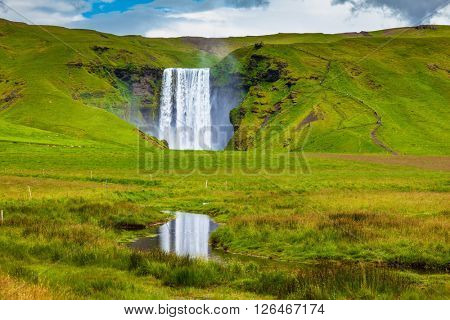 Grandiose reflection. The huge deep falls Skogafoss are reflected in small stream
