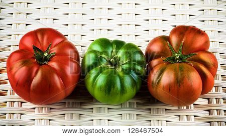 Red Green and Orange Raw Ripe Tomatoes with Stems closeup on White Wicker background. Sort Fields Raf